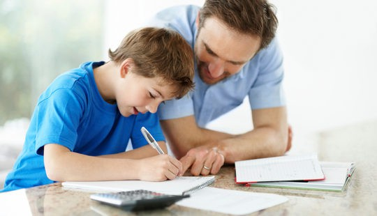 Padre ayudando a hacer los deberes a su hijo