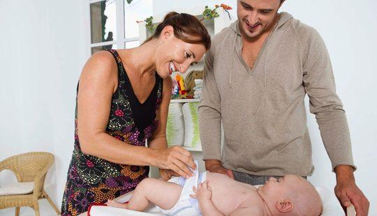 Una pareja cambia el pañal a su bebé