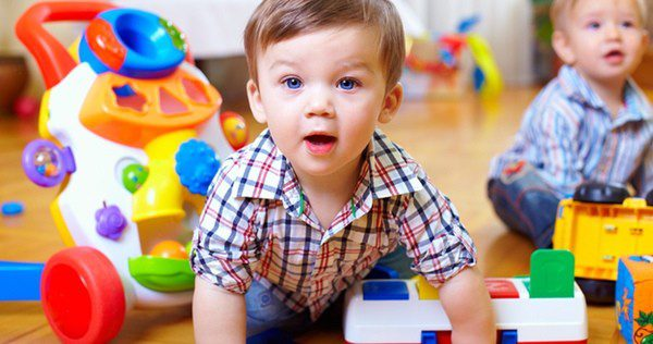 Bebé gateando rodeado de juguetes